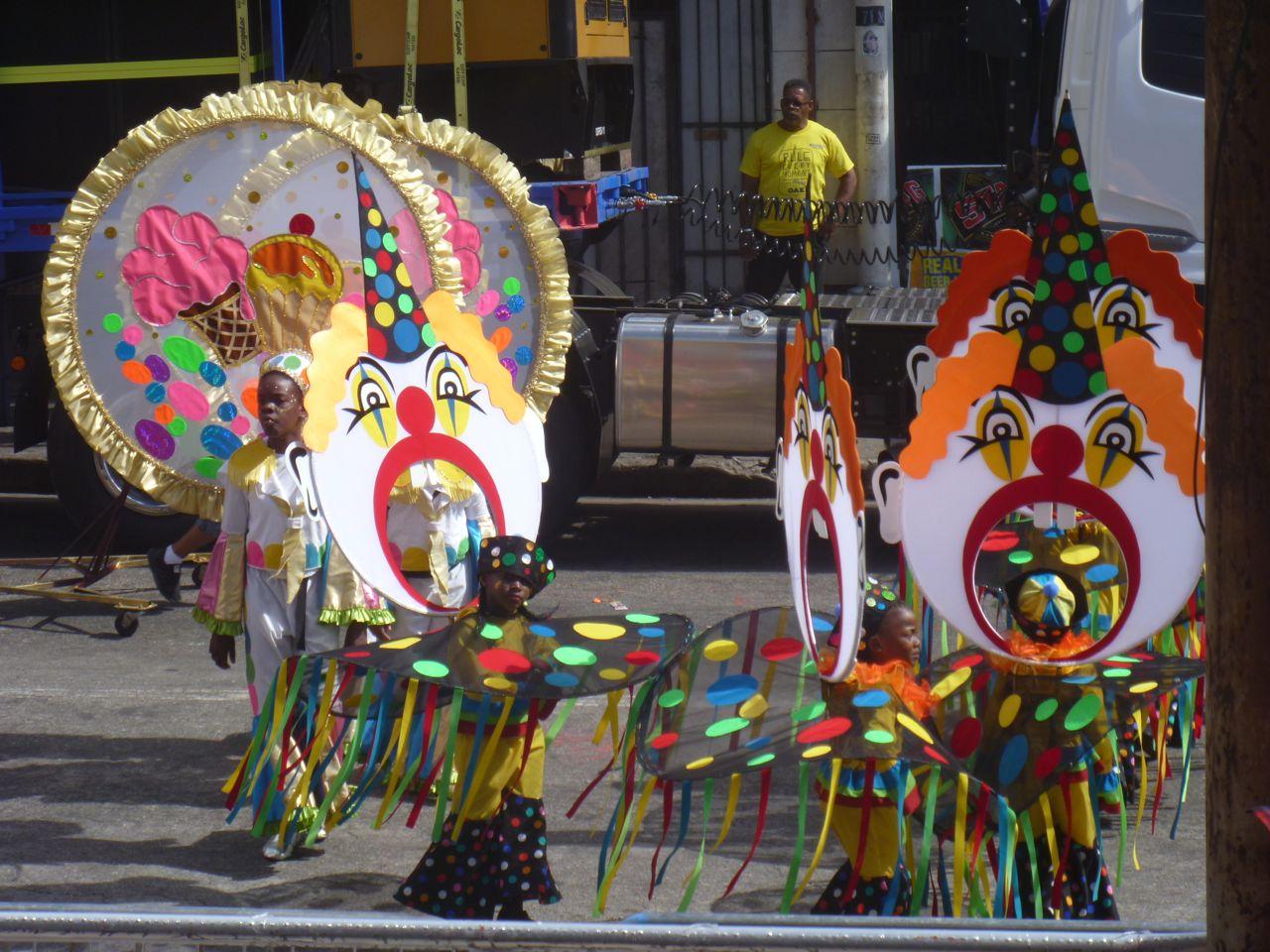 Kinder in einem Clown-Kostüm laufen bei der Grande Parade in Trinidad mit