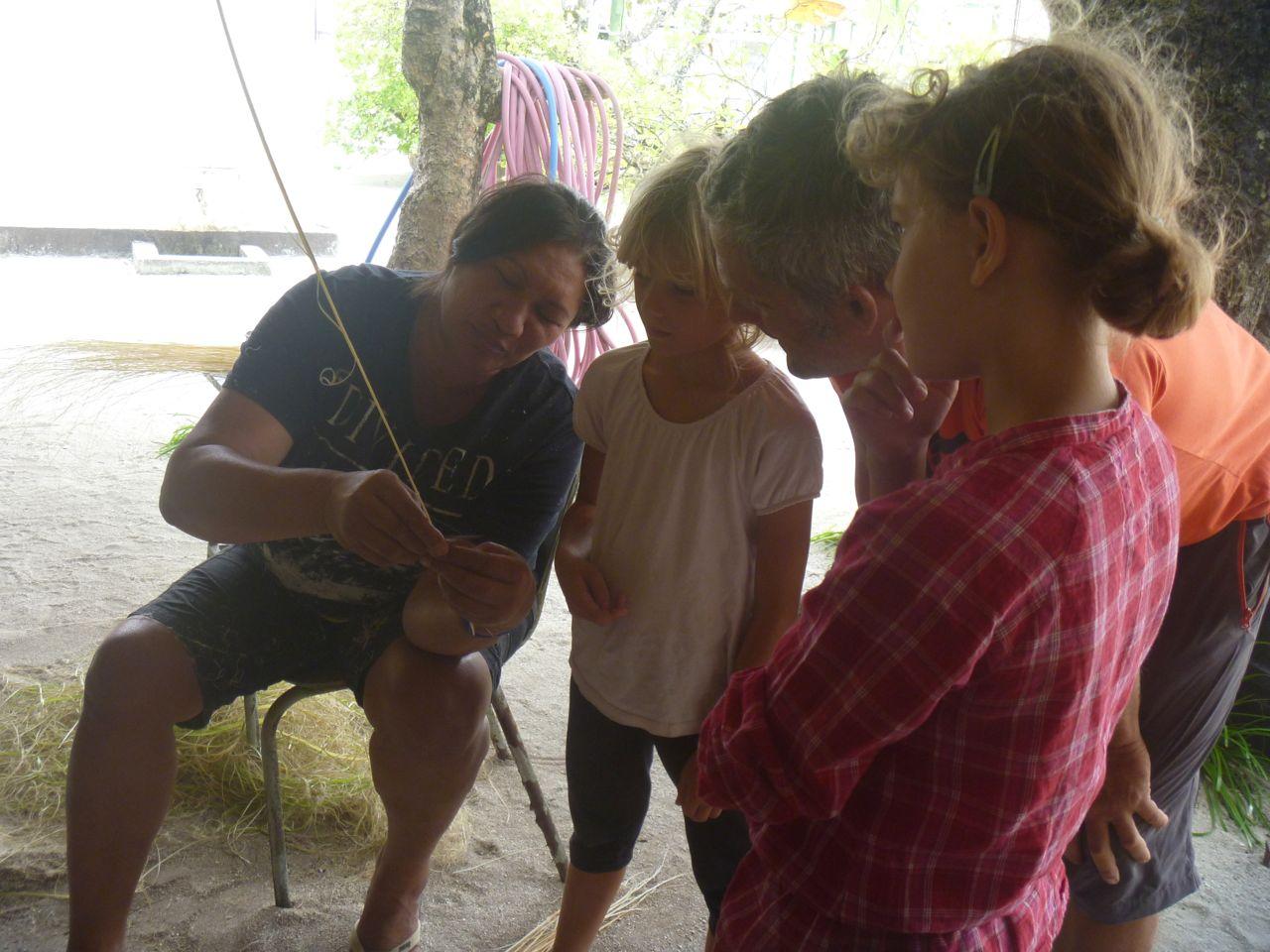 Eine Frau zeigt den Kindern, wie man die Borsten für einen Besen aus Palmenblättern herstellt.