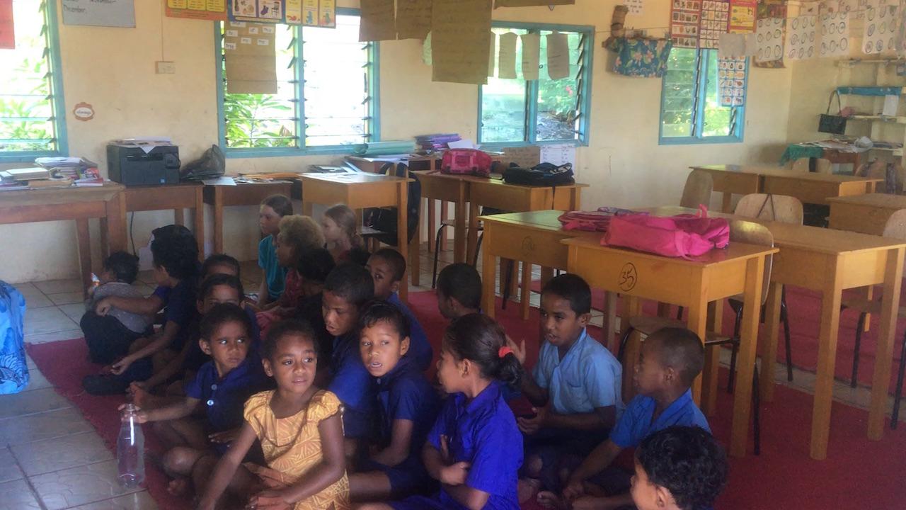 Die Kinder sitzen während des Unterrichtes auf Komo auf dem Boden