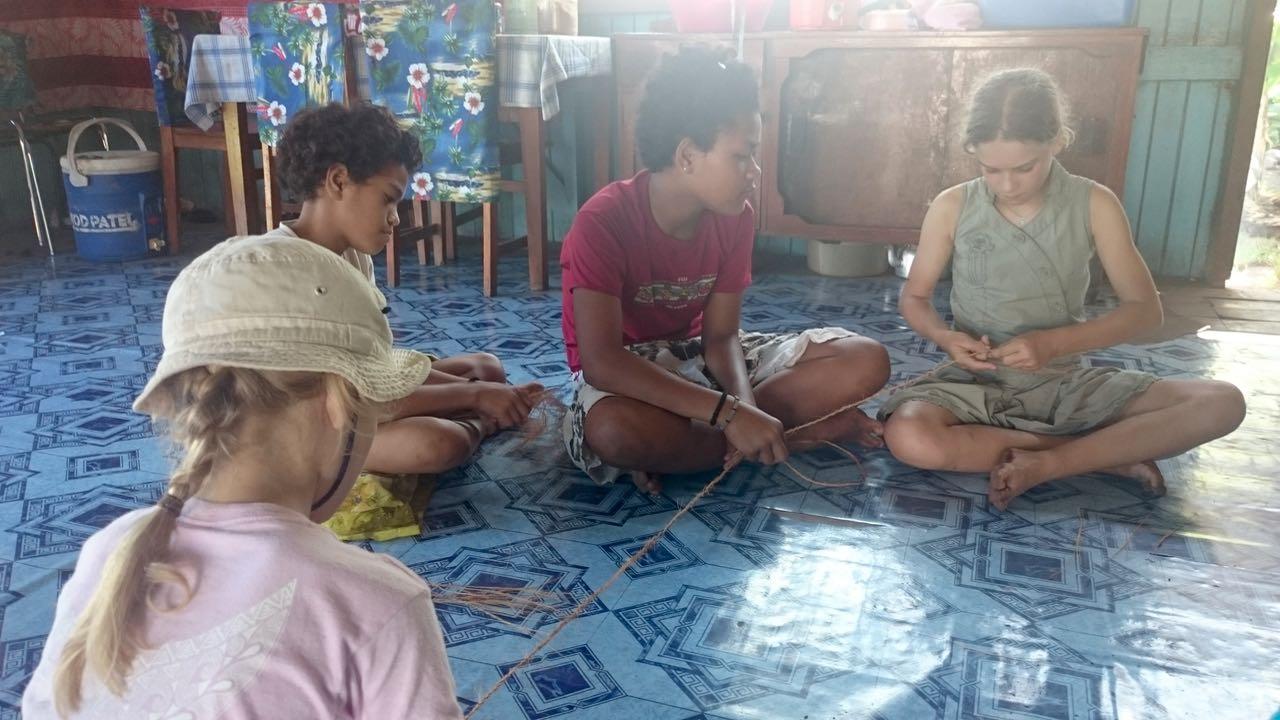 Die Kinder sind schnell dabei, der Tochter von Metui zu helfen, beim Flechten von Schnüren aus Kokosfasern.