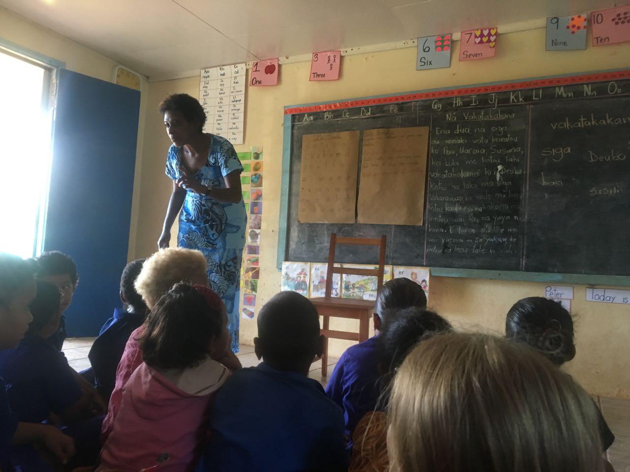Wir sitzen auf Komo im unterricht von Asi, einer der Lehrerinnen