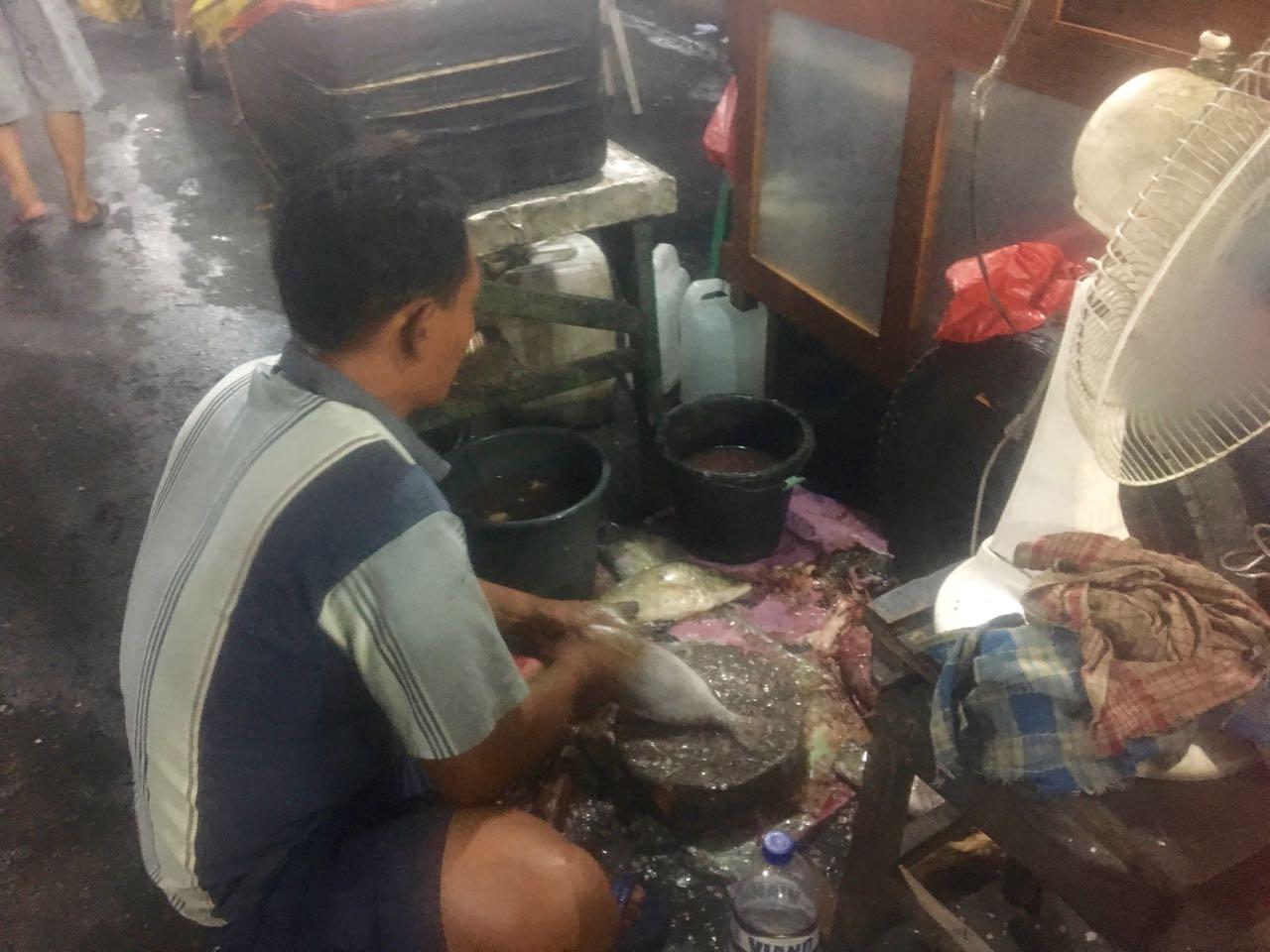 Hier wird der Fisch geschuppt, der wenig spätr auf den Grill kommt